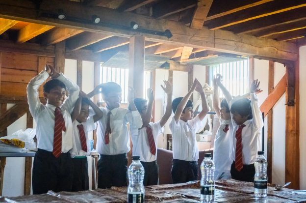 Image of young children in school uniform with their hands raised during a schools session.