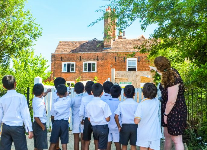 School children and workshop leader pointing at Manor House
