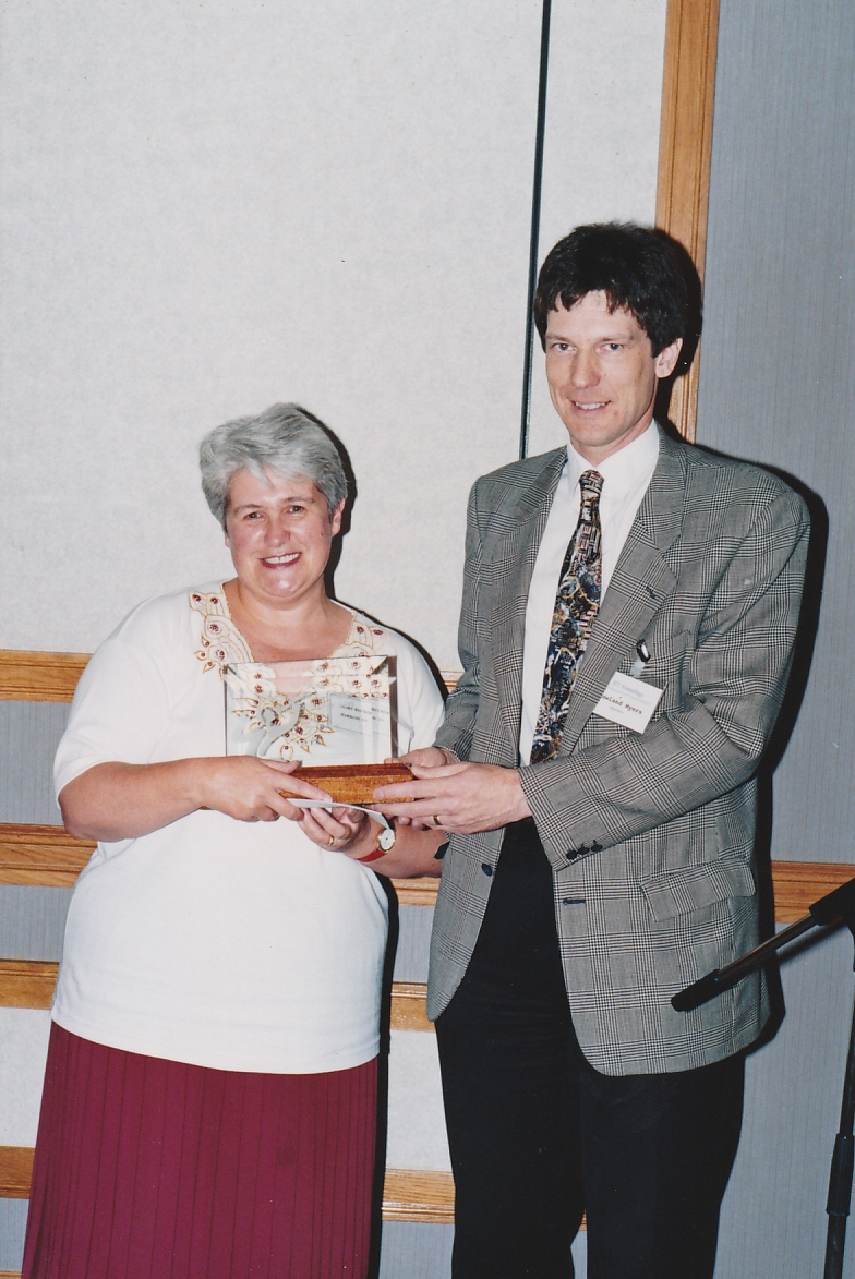 Mary receiving the award for the best magazine from Roland Myers in 1995 at the Swansea Conference of the Talking Newspaper Association of the UK